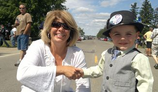 """This handout photo released by the Tufts family shows Mayor Robert """"Bobby"""" Tufts, right, shaking hands with and unidentified woman in Dorset, Minn. Tufts hasn't made it to preschool yet, but he's already been elected twice as mayor of a tiny tourist town in northern Minnesota. (AP Photo/Courtesy Tufts Family)"""