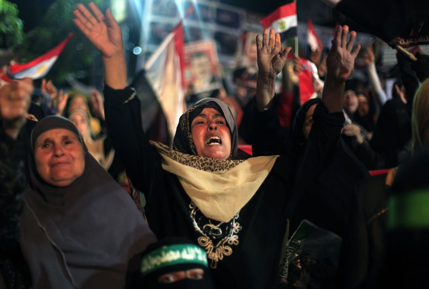Supporters of Egypt's ousted President Mohammed Morsi chant slogans during a protest outside Rabaah al-Adawiya mosque, where protesters have installed a camp and hold daily rallies at Nasr City in Cairo, Egypt, Sunday, Aug. 4, 2013. (AP Photo/Khalil Hamra)