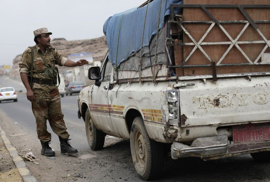 A Yemeni soldier stops a car at a checkpoint in a street leading to the U.S. embassy in Sanaa, Yemen, Sunday, Aug. 4, 2013. (AP Photo/Hani Mohammed)