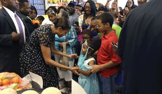 """**FILE** First lady Michelle Obama hugs Naomi Bouie, 5, as she visits Sterling Farms Grocery Store in Marrero, La., on July 23, 2013. The store was opened last year by actor Wendell Pierce as part of the """"Alliance For A Healthier Generation."""" (Associated Press"""