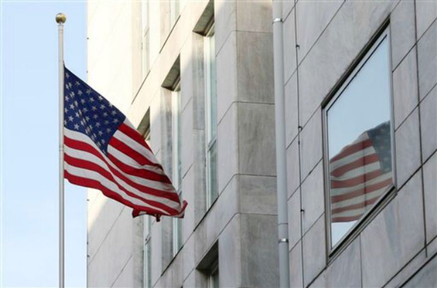 An American flag flies outside the U.S. Consulate in Milan, Italy, Tuesday, Aug. 6, 2013. Anti-terrorism police in Milan say the city's U.S. Consulate has been evacuated after receiving a letter containing a bomb threat. (AP Photo/Antonio Calanni)