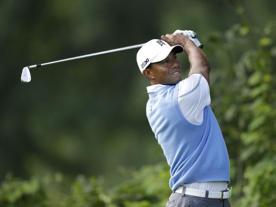 Tiger Woods hits off the15th tee during a practice round for the PGA Championship golf tournament at Oak Hill Country Club, Tuesday, Aug. 6, 2013, in Pittsford, N.Y. (AP Photo/Charlie Neibergall)