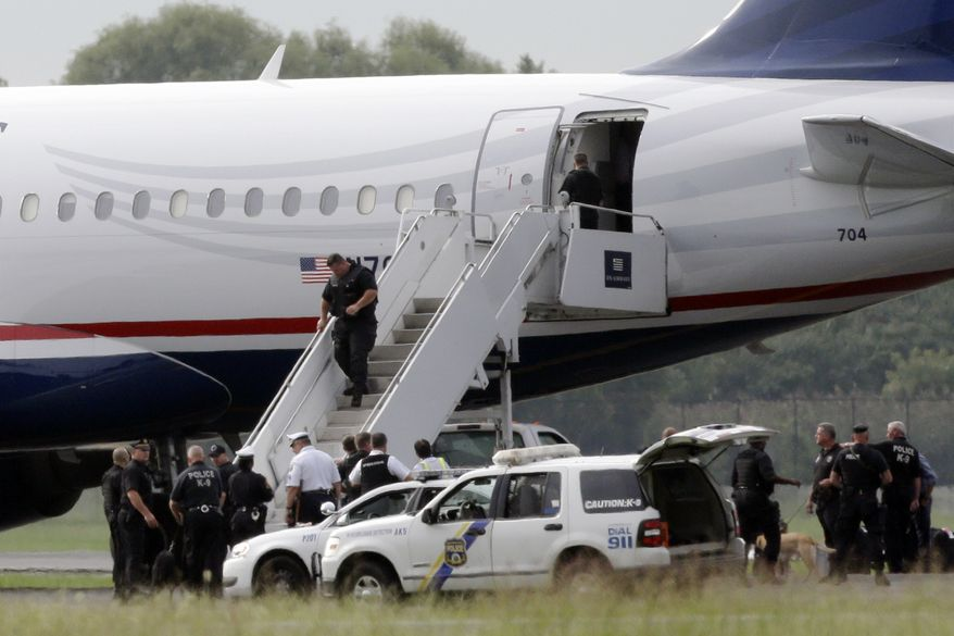 **FILE** Law enforcement officials work around a US Airways flight at Philadelphia International Airport after the plane returned to the airport on Sept. 6, 2012. A security scare that prompted authorities to recall an airborne U.S. flight was the result of an apparent hoax, police said. (Associated Press)