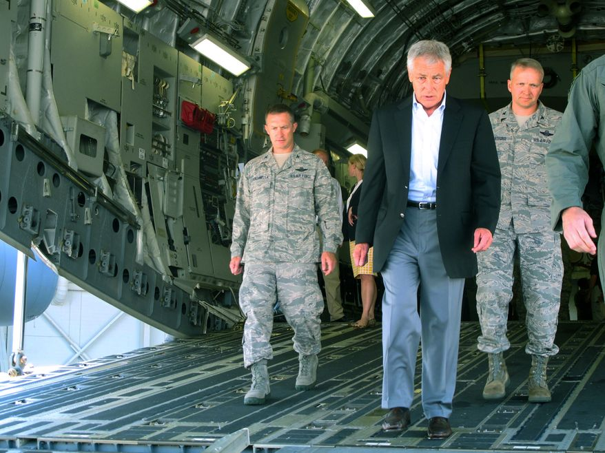 **FILE** Defense Secretary Chuck Hagel, flanked by Air Force personnel, walks down the rear ramp of a C-17 at Joint Base Charleston near Charleston, S.C., on July 17, 2013, the last day of a three-day trip to visit bases in the Carolinas and Florida. (Associate Press)