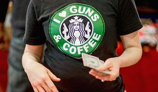 Sandy Early, with Free State Militia Firearms, sells T-shirts that modify the Starbucks logo at a gun show in Annapolis earlier this year. (Andrew Harnik/The Washington Times)