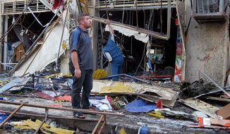 People inspect the scene of a car bomb attack in the commercial area of Karradah in Baghdad on Tuesday. A wave of bombings, mainly targeting markets in and near Baghdad killing scores, officials said, the latest in a surge of violence that has gripped Iraq. (Associated Press)