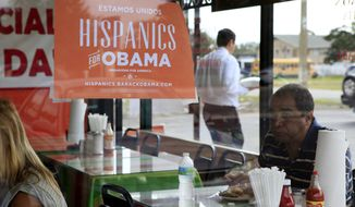 """**FILE** Spanish language election campaign signs promoting President Obama hang on the windows at Lechonera El Barrio Restaurant in Orlando, Fla., on Oct. 26, 2012. The sign reads """"We are united. Hispanics for Obama."""" (Associated Press)"""
