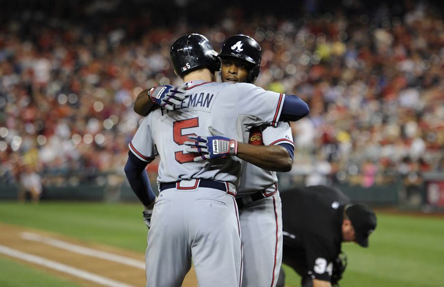 Atlanta Braves' Justin Upton, right, gets a hug from teammate Freddie Freeman (5) after hitting a home run against the Washington Nationals during the seventh inning of a baseball game on Wednesday, Aug. 7, 2013, in Washington. (AP Photo/Nick Wass)