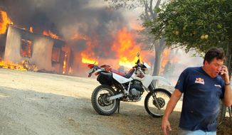 Twin Pines, Calif. resident Dave Clark tells some neighbors their home is OK while his own house burns behind him, Wednesday, Aug. 7, 2013, near Banning, Calif. A new wildfire has broken out in Riverside County near Banning, sending up a massive plume of smoke and surging toward three communities where people have been told to evacuate. (AP Photo/The Desert Sun, Richard Lui)