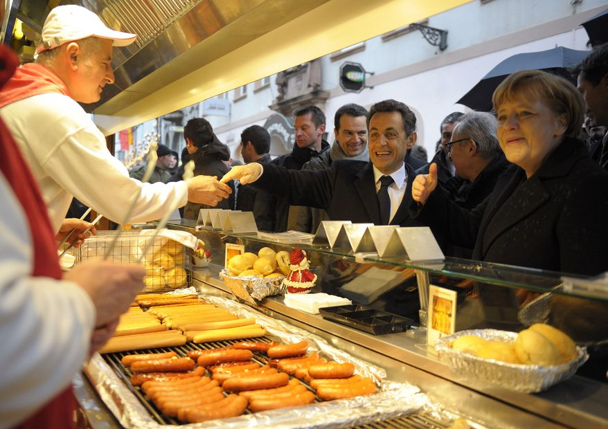 **FILE** French President Nicolas Sarkozy (center) and German Chancellor Angela Merkel (right) stop at a roast sausage fast food stand as they visit the Christmas market in Freiburg, Germany, on Dec.  10, 2010. (Associated Press)
