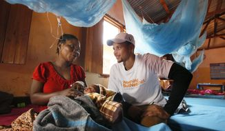 In this photo provided by United Nations Foundation, NBA superstar Stephen Curry talks to a mother recovering from malaria, holding her newborn baby, at a health facility in the Nyarugusu Refugee Camp in Tanzania, during a Nothing But Nets trip to distribute anti-malaria bed nets, Tuesday, July 30, 2013. (AP Photo/United Nations Foundation, Insider Images/Stuart Ramson)