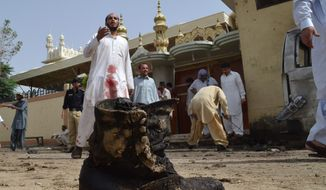 Pakistani investigators collect evidence at the site of a bomb attack in Quetta, Pakistan, Thursday, Aug. 8, 2013. A suicide bomber attacked a funeral for a policeman in southwestern Pakistan on Thursday, killing tens of people, including a senior police officer, and wounding over 60, police said. (AP Photo/Arshad Butt)