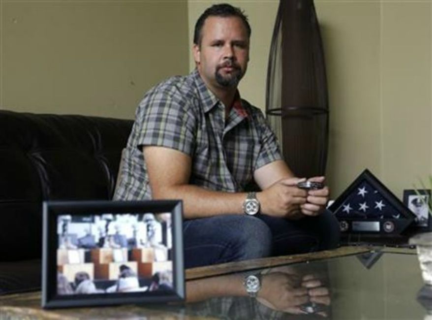 ** FILE **  Retired U.S. Army Staff Sgt. Shawn Manning poses for a photo at his home in Lacey, Wash., as he holds a photograph from the memorial for victims of the 2009 mass shooting at Fort Hood, Texas, Aug. 3,, 2013. Manning, who still carries two bullets in his body from the shooting that killed 13 people, estimates he has lost $2,000 a month in pay and benefits because of the decision to classify the injuries as resulting from workplace violence rather than combat or terrorist-related. (AP Photo/Ted S. Warren, File)