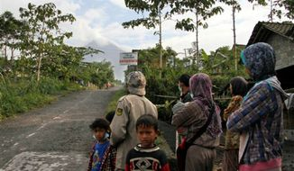 Villagers look at Merapi volcano Cangkringan, Indonesia, Monday, July 22, 2013. Indonesia's most volatile volcano spewed smoke and ash Monday, forcing hundreds of people to flee their villages along its slopes, a disaster official said. (AP Photo/Slamet Riyadi)
