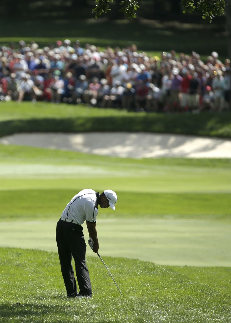 Tiger Woods hits out of the rough on the first hole during the third round of the PGA Championship golf tournament at Oak Hill Country Club, Saturday, Aug. 10, 2013, in Pittsford, N.Y. (AP Photo/Charlie Riedel)
