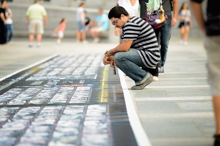 "Jamime Negron [cq] of New York, N.Y. looks at a 150-foot ""Wall of Honor"" poster that includes photos of World War II veterans during Spirit of '45 Day ceremonies at the World War II Memorial on the National Mall, Washington, D.C., Sunday, August 11, 2013. (Andrew Harnik/The Washington Times)"