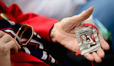Dorothy May of Shepherdstown, W.Va., one of the many women who got jobs in factories supplying the war effort, holds a medal she received for her service.