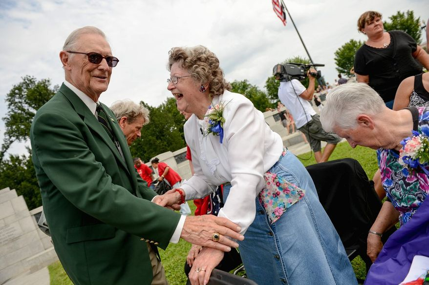 Crena Anderson of Hagerstown, Md., who worked as a riveter in a factory during World War II, is greeted by retired Gen. Frederick J. Kroesen, Jr., near the 150-foot Wall of Honor poster displayed during Spirit of '45 Day ceremonies at the World War II Memorial on the Mall. The day honors all who supported the war effort. (Andrew Harnik/The Washington Times)