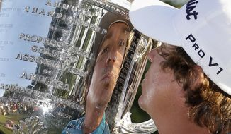 Jason Dufner kisses the Wanamaker Trophy after winning the PGA Championship golf tournament at Oak Hill Country Club, Sunday, Aug. 11, 2013, in Pittsford, N.Y. (AP Photo/Julio Cortez)