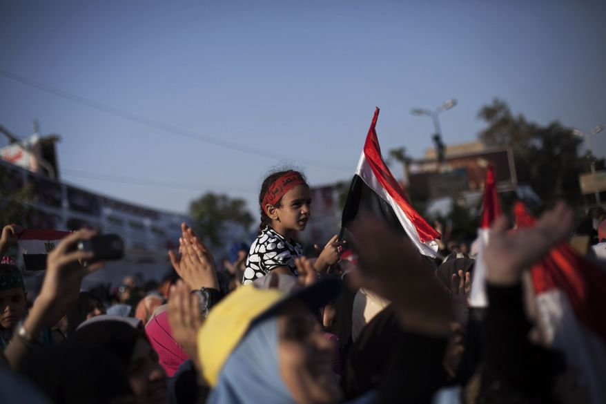 An Egyptian girl waves a national flag while supporters of Egypt's ousted President Mohammed Morsi chant slogans against the Egyptian Army at the sit-in at Rabaah al-Adawiya mosque, which is fortified with multiple walls of bricks, tires, metal barricades and sandbags, and where protesters have installed their camp in Nasr City, Cairo, Egypt, Sunday, Aug. 11, 2013. (AP Photo/Manu Brabo)