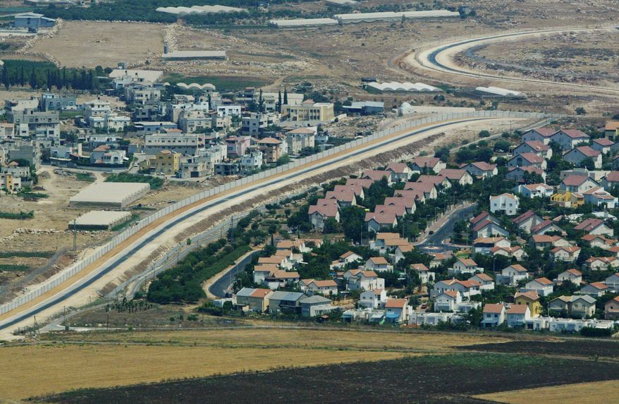 ** FILE ** This Tuesday, July 29, 2003, file photo is an aerial view over West Bank showing a Palestinian village, left, and a Jewish settlement, right, separated by a wall, part of the separation fence Israel is building. (AP Photo/Lefteris Pitarakis)