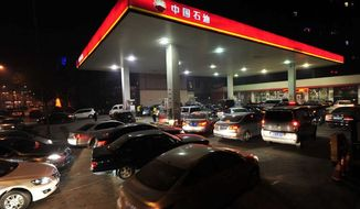 Pumped up: Fuel-hungry cars line up at a gas station in China, the world's largest market for autos since 2009. The burgeoning demand is causing China's estimated consumption of oil to surge to 11 million barrels a day next year. (Associated Press Photographs)