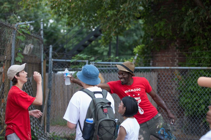 Aniekan Udofia laughs with his apprentices during a break from priming the wall for his mural on Florida Avenue Northwest that is part of a graffiti-prevention program. (Andrew S. Geraci/The Washington Times)