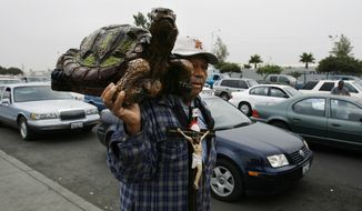 **FILE** Manuel Ibanez, 84, sells ceramic turtles and crucifixes at the Otay border crossing in Tijuana, Mexico, on July 17, 2008. (Associated Press)