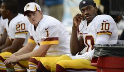 Washington Redskins quarterback Robert Griffin III (10) and kicker John Potter (1) watch from the bench in the first quarter of a preseason NFL football game between the Redskins and the Tennessee Titans on Thursday, Aug. 8, 2013, in Nashville, Tenn. (AP Photo/Mark Zaleski)