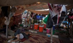 Supporters of Egypt's ousted President Mohammed Morsi rest in a tent watching TV on Tuesday outside Rabaah al-Adawiya mosque, where protesters have installed a camp and held daily rallies at Nasr City in Cairo. Instead of rushing for the exits, Islamist supporters are replacing tents with wooden huts in their Cairo encampment. (Associated Press)