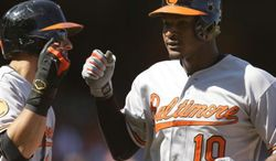 Baltimore Orioles' Adam Jones, right, is congratulated after hitting a three-run home run off San Francisco Giants' Barry Zito in the ninth inning of a baseball game on Sunday, Aug. 11, 2013, in San Francisco. (AP Photo/Ben Margot)