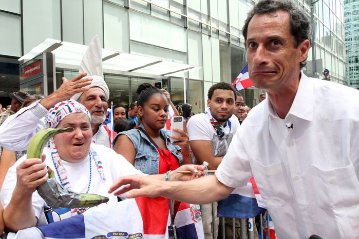 Former Rep. Anthony Weiner, a Democratic candidate for New York City mayor, reacts after sharing a moment with a spectator and her plantains as he takes part in the Dominican Day Parade on New York's Avenue of the Americas on Sunday, Aug. 11, 2013. (Associated Press)