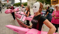 Ali McCracken, right, and others with Code Pink wear pink drones as they protest outside the Association for Unmanned Vehicle Systems International 2013 conference held at the Washington Convention Center, Washington, D.C., Tuesday, August 13, 2013. (Andrew Harnik/The Washington Times)
