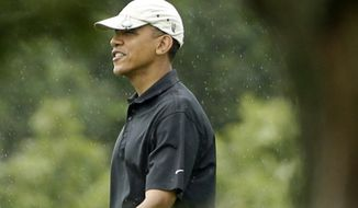 President Barack Obama golfs as a light rain falls at Vineyard Golf Club in Edgartown, Mass., on the island of Martha's Vineyard Monday, Aug. 12, 2013. (AP Photo/Steven Senne)
