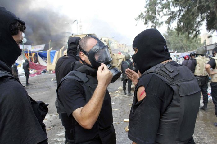 A lightly wounded member of the Egyptian security forces talks with other officers as clear they clear the smaller of the two sit-ins by supporters of ousted Islamist President Mohammed Morsi, near the Cairo University campus in Giza, Cairo, Egypt, Wednesday, Aug. 14, 2013. (AP Photo/Imad Abdul Rahman)