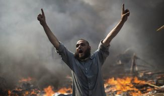 A supporter of ousted Islamist President Mohammed Morsi shouts during clashes with Egyptian security forces in Cairo's Nasr City district, Egypt, Wednesday, Aug. 14, 2013. Egyptian police in riot gear swept in with armored vehicles and bulldozers Wednesday to clear two sprawling encampments of supporters of the country's ousted Islamist president in Cairo, showering protesters with tear gas as the sound of gunfire rang out. (AP Photo/Manu Brabo)