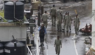 Indian navy sailors walk at the naval dockyard where a submarine caught fire and sank after an explosion early Wednesday in Mumbai, India, Wednesday, Aug. 14, 2013. (AP Photo/Rafiq Maqbool)
