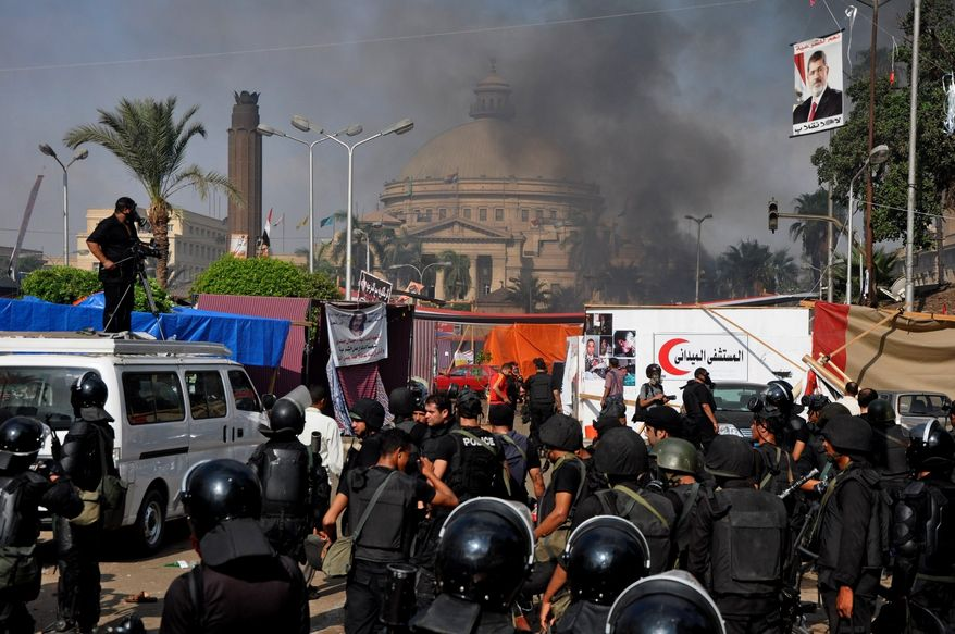 Egyptian security forces clear a sit-in camp set up by supporters of ousted Islamist President Mohammed Morsi near Cairo University in Cairo's Giza district, Egypt, Wednesday, Aug. 14, 2013. Egyptian police in riot gear swept in with armored vehicles and bulldozers Wednesday to clear the sit-in camp and the other encampment set up by supporters of the country's ousted Islamist president in Cairo, showering protesters with tear gas as the sound of gunfire rang out. (AP Photo/Hussein Tallal)