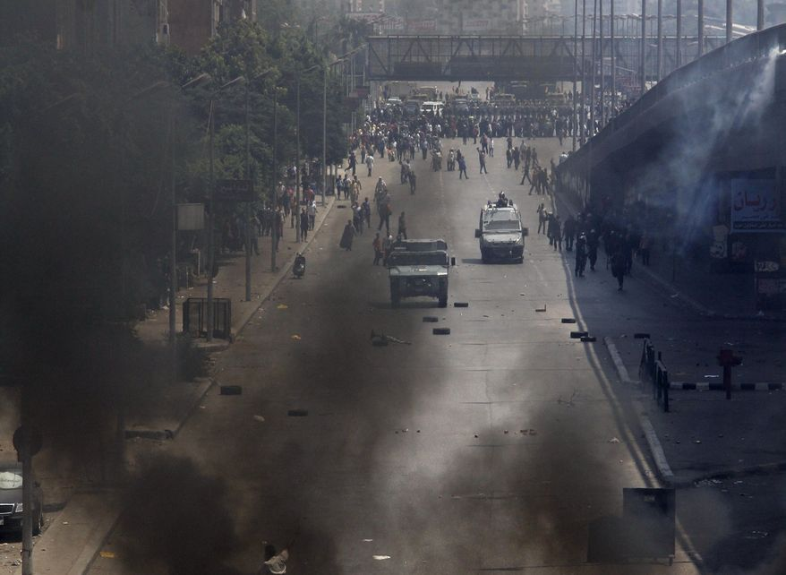 Egyptian security forces clear a sit-in camp set up by supporters of ousted Islamist President Mohammed Morsi near Cairo University in Cairo's Giza district, Egypt, Wednesday, Aug. 14, 2013. Egyptian police in riot gear swept in with armored vehicles and bulldozers Wednesday to clear the sit-in and the other encampment of supporters of the country's ousted Islamist president in Cairo, showering protesters with tear gas as the sound of gunfire rang out. (AP Photo/Mohammed Asad)