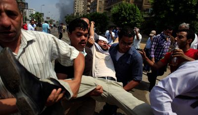 "Mass Violence: Supporters of Mr. Morsi carry a wounded man through the mayhem. As the Egyptian military appeared to claim more power, a White House spokesman warned that ""The world is watching."""