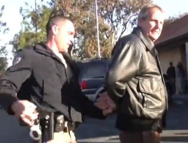 "Mark Mackey is arrested outside a California DMV in 2011 for reading a bible out loud to ""a captive audience."" All charges have been dropped against him. (Image: YouTube)"