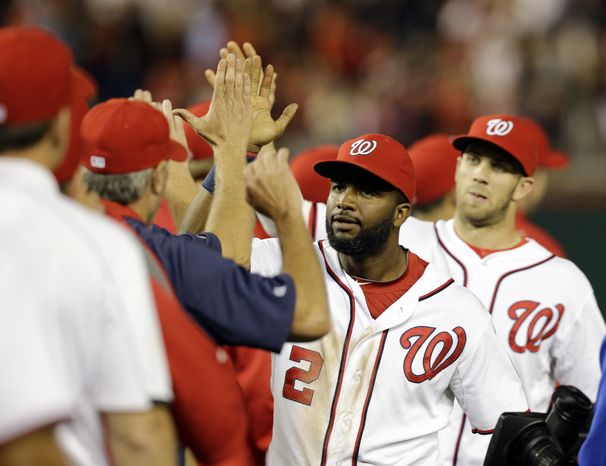 The Washington Nationals celebrate their fifth straight victory on Wednesday night. (Associated Press photo)