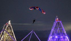 ** FILE ** In this July 27, 2012, file photo, British stuntman Mark Sutton, parachuting into the Olympic Stadium, dressed as James Bond, during the Olympic Games 2012 Opening Ceremony. He has been killed in an accident in the Swiss Alps while flying a special wing suit. Swiss police confirmed that a 42-year-old Briton died Wednesday, Aug. 14, 2013, in a fall near Trient in the Valais region. (AP Photo/PA, Lewis Whyld, File)