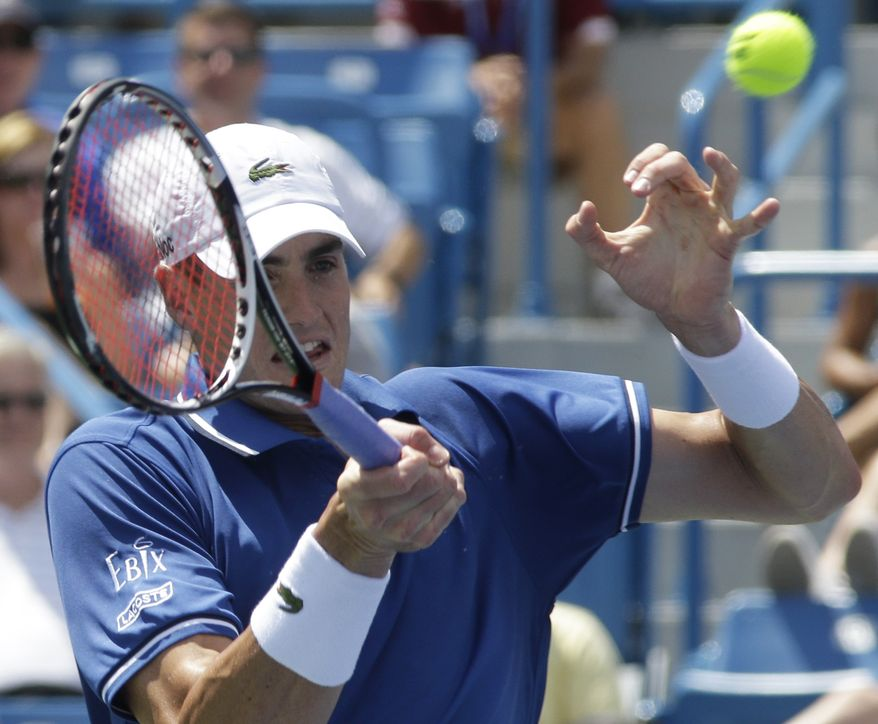 John Isner hits a forehand against Novak Djokovic, from Serbia, during a quarterfinal match at the Western & Southern Open tennis tournament, Friday, Aug. 16, 2013, in Mason, Ohio. (AP Photo/Al Behrman)