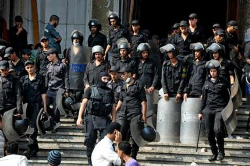 Egyptians security forces provide a cordon around the al-Fatah mosque, after hundreds of Muslim Brotherhood supporters barricaded themselves inside the mosque overnight, following a day of fierce street battles that left scores of people dead, near Ramses Square in downtown Cairo, Egypt, Saturday, Aug. 17, 2013. (AP Photo/Hussein Tallal)