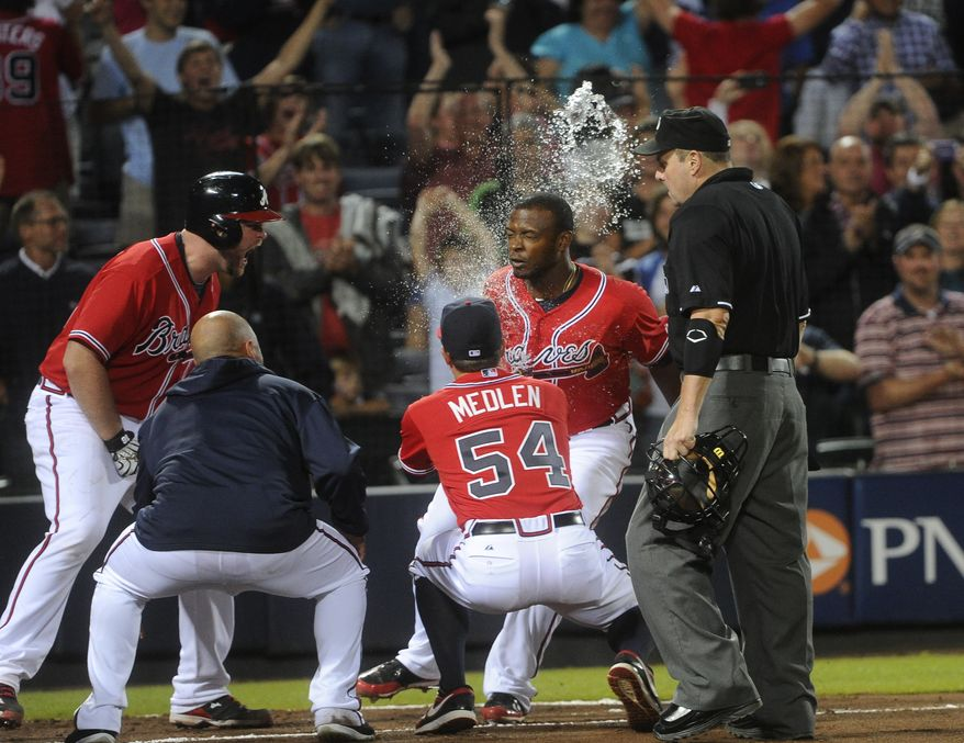 The Atlanta Braves celebrate after Justin Upton hit a walk-off home run to beat the Washington Nationals on Friday night. (Associated Press photo)