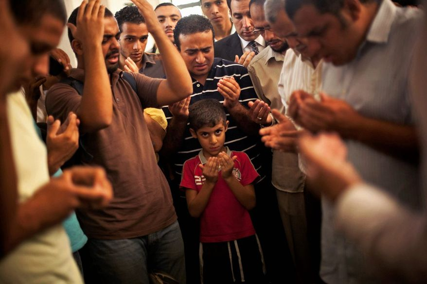 Mass Mourning: A son of Ammar Badie prays during his father's funeral Sunday. Mr. Badie, a son of the Muslim Brotherhood's spiritual leader Mohammed Badie, was killed by Egyptian security forces Friday during clashes in Cairo. (Associated Press)