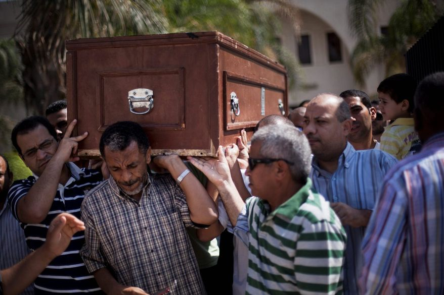 Friends and relatives of Ammar Badie, 38 and son of Muslim Brotherhood's spiritual leader Mohammed Badie, killed Friday by Egyptian security forces during clashes in Ramses Square, carry his coffin during his funeral in al-Hamed mosque in Cairo on Sunday. Egypt increased security at the Supreme Constitutional Court building ahead of planned mass rallies by supporters of ousted President Mohammed Morsi. (Associated Press)