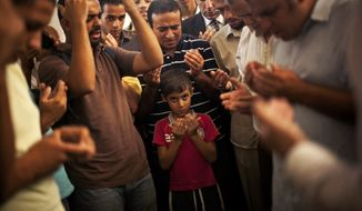A son of the late Ammar Badie prays during his father's funeral in al-Hamed mosque in Cairo's Katameya district on Aug. 18, 2013. Badie, the son of Muslim Brotherhood's spiritual leader Mohammed Badie, was killed by Egyptian security forces two days earlier during clashes in Cairo's Ramses Square. (Associated Press)