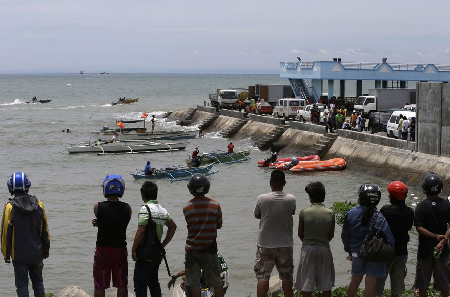 A crowd watches as divers continue their search and rescue operation off Talisay coast, Cebu province on Aug. 18, 2013 following a collision of the passenger ferry MV Thomas Aquinas and the cargo ship MV Sulpicio Express Siete in central Philippines on Aug. 16. Divers plucked two more bodies from the sunken passenger ferry on Sunday and scrambled to plug an oil leak in the wreckage after a collision with a cargo ship. The accident near the central Philippine port of Cebu that has left 34 dead and more than 80 others missing. (Associated Press)